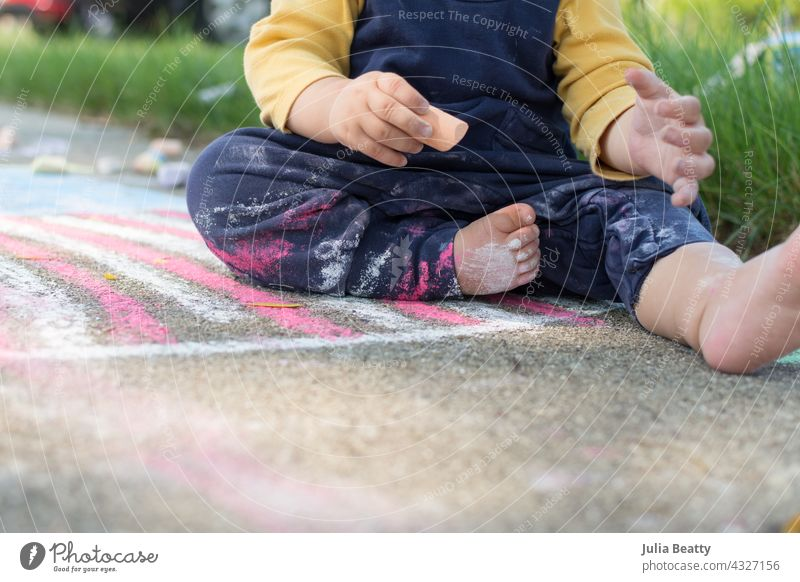 13 month old baby holding a piece of sidewalk chalk, toddler sits on a drawing of the American Flag and has chalk dust on pants and body 4th of july