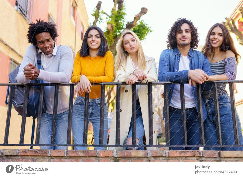 Multiracial group of young people talking together in the street. students multi-ethnic socializing diversity friends multiracial outdoors outside urban men