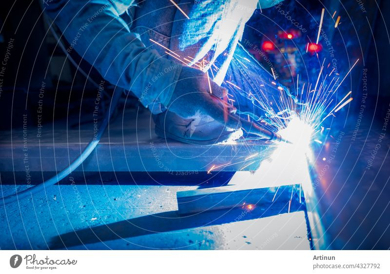 Welder welding metal with argon arc welding machine and has welding sparks. A man wears protective gloves. Safety in industrial workplace. Welder working with safety. Worker in steel industry factory.