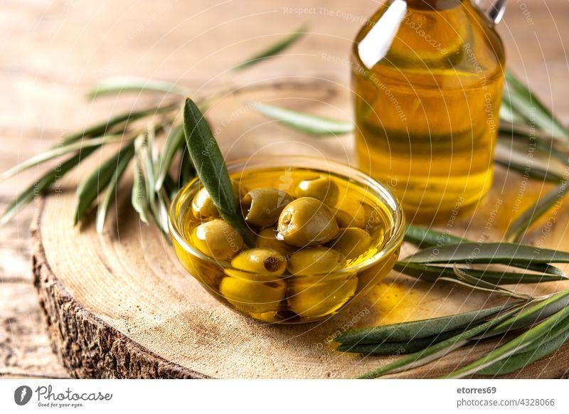 Virgin olive oil bottle and green olives food fresh glass golden healthy ingredient italian leaves liquid mediterranean natural spain table vegan vegetarian