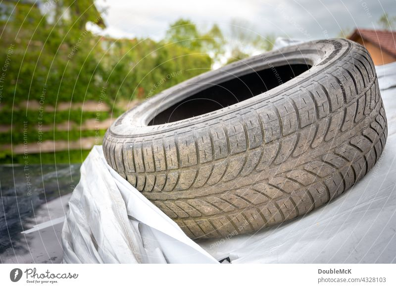 Dirty car tire lies on car tarp Car Vehicle Means of transport Transport Road traffic Motoring Colour photo Exterior shot Deserted Day Mobility Broken
