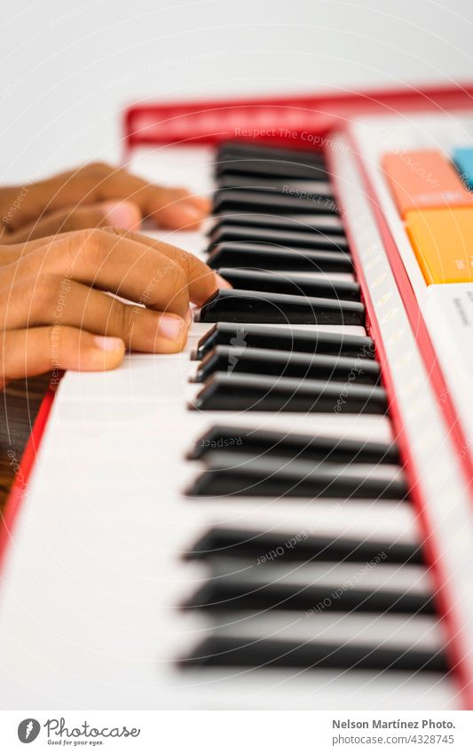 Close-up of the fingers of a little kid playing in a red piano pianist person chord girl classical rythm create practicing performance melody creative closeup