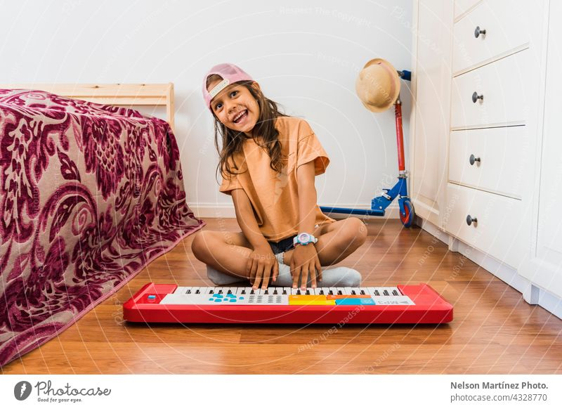 Happy hispanic girl wearing a pink cup playing in a red piano in her bedroom pianist person chord classical finger rythm create practicing performance melody