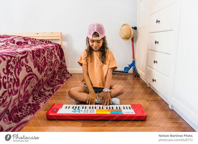 Little hispanic girl wearing a pink cup playing in a red piano in her bedroom pianist person chord classical finger rythm create practicing performance melody