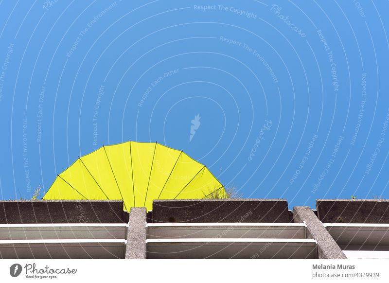 Abstract architecture, yellow sun umbrella on the roof terrace, summer vibe, bottom view. Blue sky abstract architecture abstract background beautiful blue