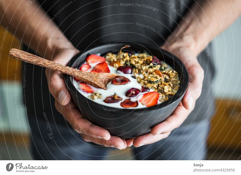 Man holds a bowl of granola, yogurt and strawberries in his hands Breakfast Yoghurt Strawberry stop subsection Cereal Healthy roasted Nut vintage Wood Diet