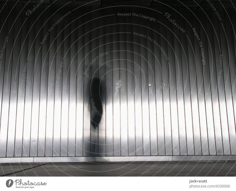 Appearance in front of a metal wall Wall (building) Modern urban Aluminium motion blur light reflexes Silhouette Structures and shapes Phenomenon Stripe