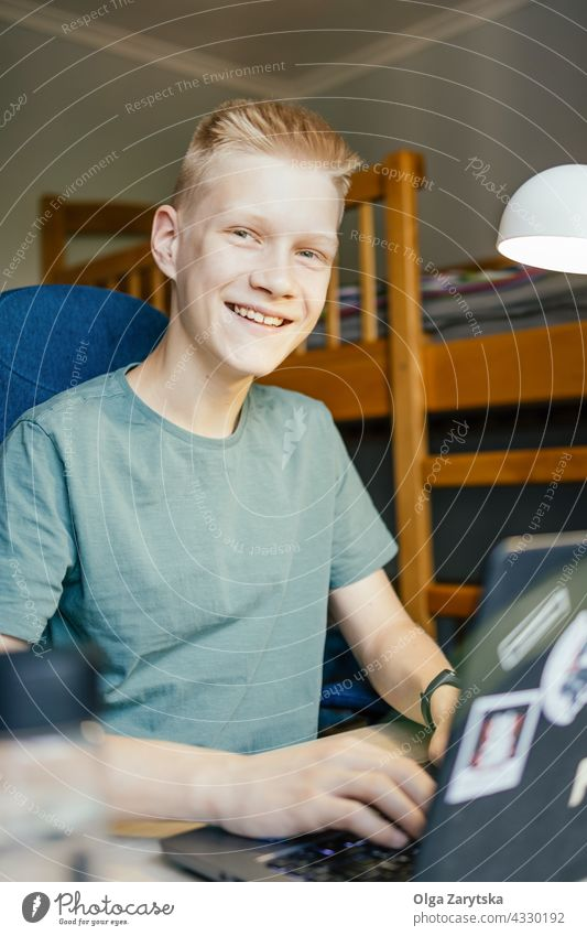 Young man smiling and looking at camera. student working online young home dormitory programmer education college studying laptop boy teenager 14-15 caucasian