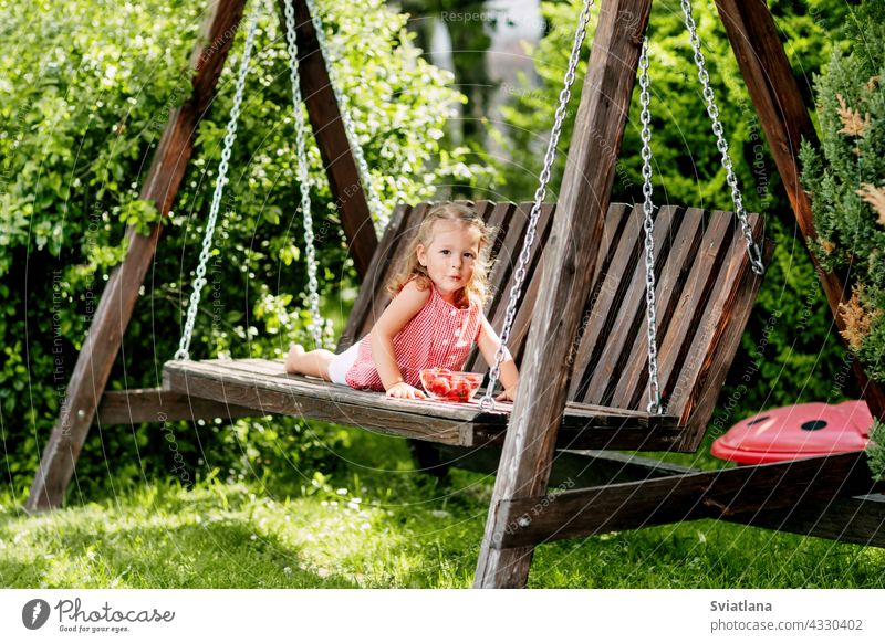 A little girl is lying on a garden swing and eating fresh strawberries baby strawberry lie down toddler summer cute fun fruit spring sunny colorful day green