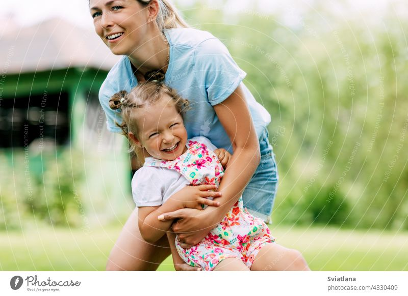 A young mother and her sweet little girl have fun in a sunny garden. The concept of a happy childhood and motherhood Baby Happy Garden mama Cute Mother Infancy