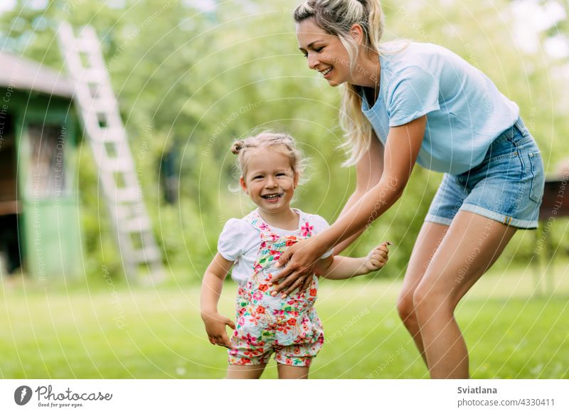 Mom and her little daughter are playing outdoors. The concept of a happy childhood and motherhood baby fun garden mom cute young girl sunny park love kid joy
