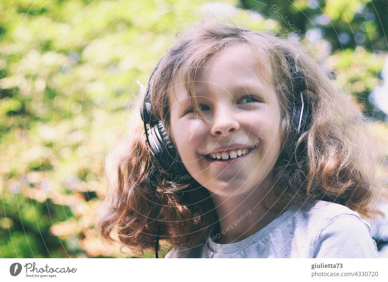 Portrait of a laughing 10 year old boy with long curly hair and headphones 10 years 11 years out Beautiful weather Laughter Happiness Funny Change naturally