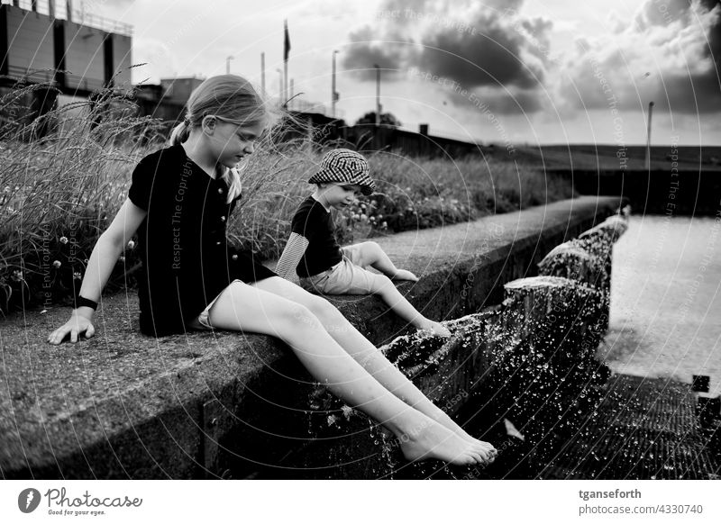 Children at the water children Water cooling Inject Cool feet quay wall dollar Drops of water Cooling Refreshment Swimming & Bathing Wet Summer Exterior shot