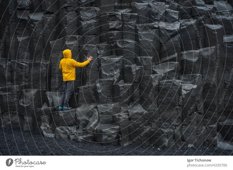 Adult man in yellow jacket standing on basalt columns on Reynisfjara Black Sand Beach in Iceland iceland reynisfjara sand beach black adult nature volcanic vik