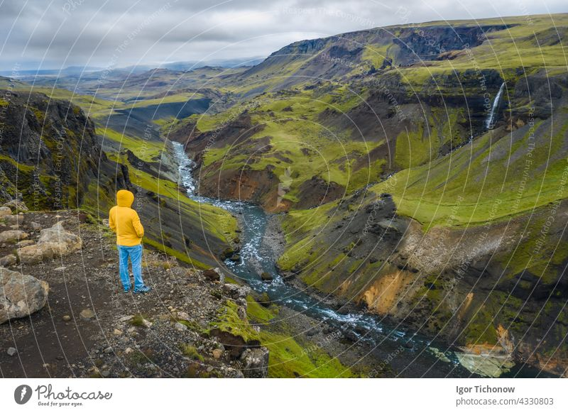 Aerial view of man enjoying Iceland landscape of highland valley and river Fossa with blue water stream and green hills and moss covered cliffs aerial above