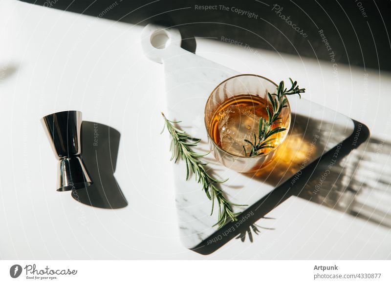 whiskey with rosemary garnish cocktail afternoon light Bourbon liquor marble kitchen scotch glass
