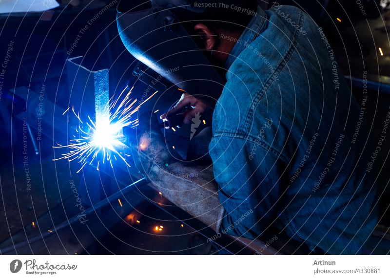 Welder welding metal with argon arc welding machine and has welding sparks. A man wears welding mask and protective gloves. Safety in industrial workplace. Welder working with safety. Steel industry.