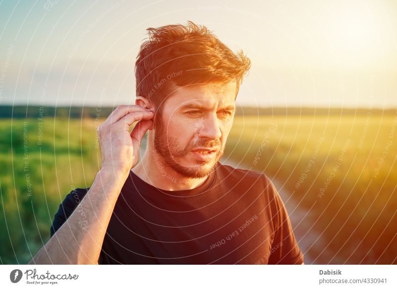 Active millenial man portrait outdoors at sunset sport caucasian lifestyle athlete fitness generation headphones beard casual exercise outside sporty young