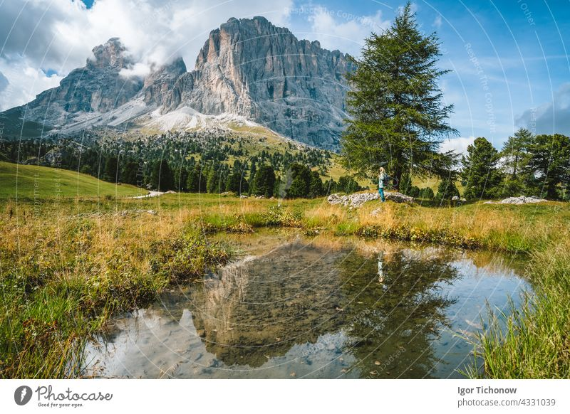 Woman hiking in Val Gardena. Pond and reflection of Sassolungo Langkofel mountain. Dolomites, Italy summer landscape dolomites woman gardena sassolungo val