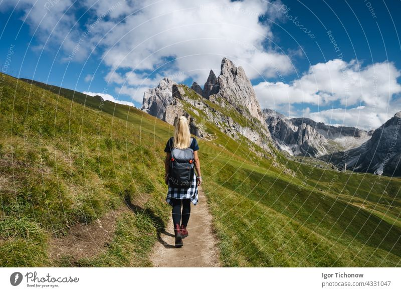 Women hiker on trail path and epic landscape of Seceda peak in Dolomites Alps, Odle mountain range, South Tyrol, Italy, Europe alps dolomites woman female italy