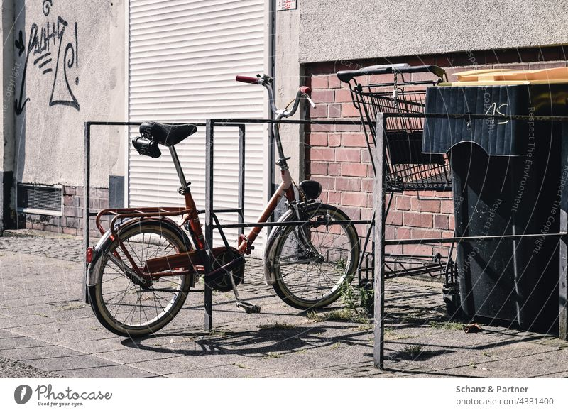 old folding bike at the bike stand Bicycle Folding bicycle Bicycle rack turnaround City life Shopping Trolley dustbin roller shutter Town Shadow