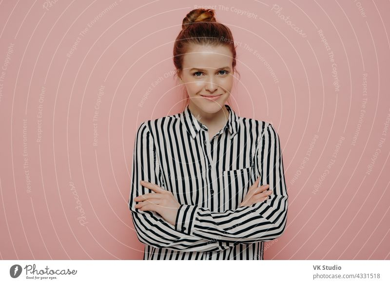 Happy teenage girl with crossed arms posing against pink studio background satisfied happy redhead woman hair bun looking straight smiling joyfully camera