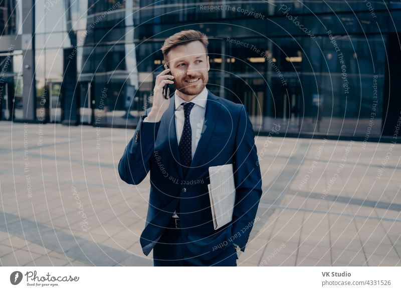 Happy office worker with newspaper talking on smartphone handsome businessman mobile call happy good smiling male blue news. hearing success. newspaper suit