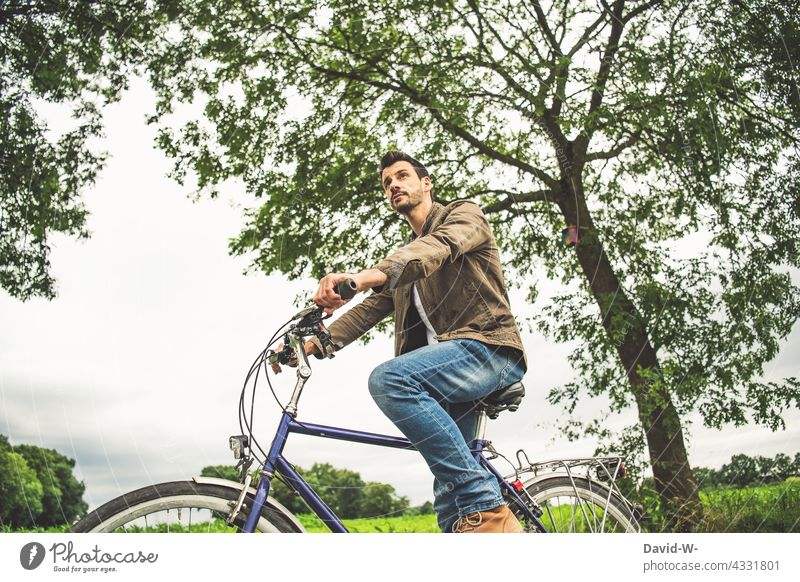 Man sitting on a bicycle Bicycle Sit Cycling tour Break think Trip out Nature Observe