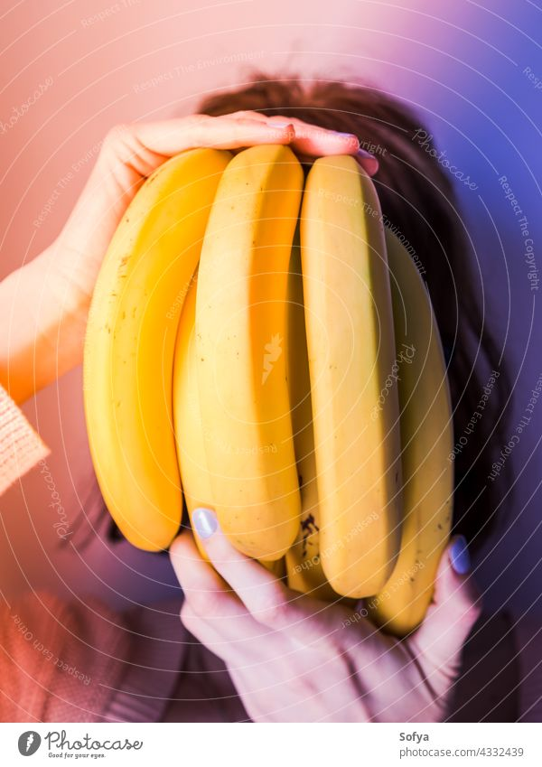 Woman covering face with bunch of bananas. Neon art woman purple hand manicure neon food design concept modern trends diet fashion gradient female color light