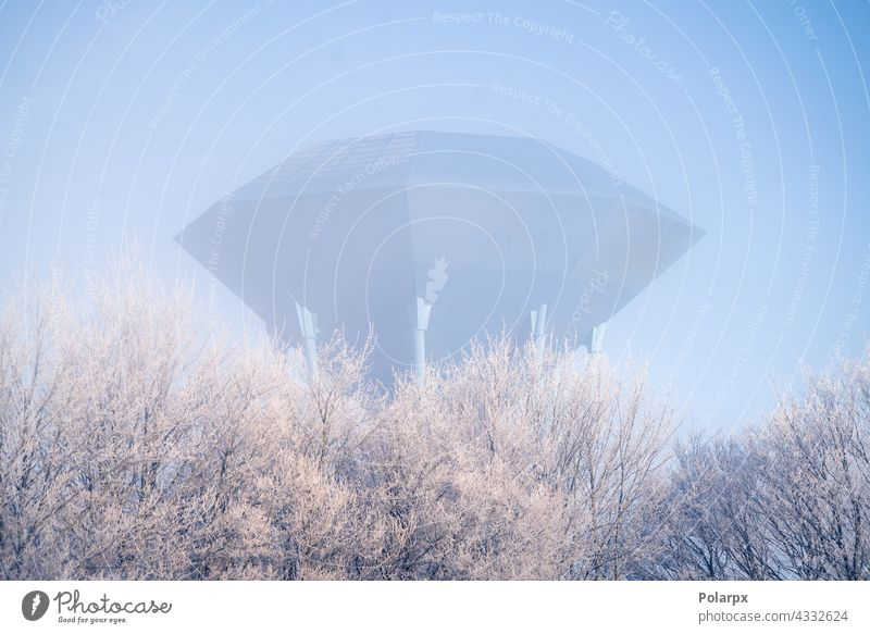 Futuristic water supply tower on cold morning day urban gallon consumption preserve aqua water tank misty fog utility object trees snow winter frost future