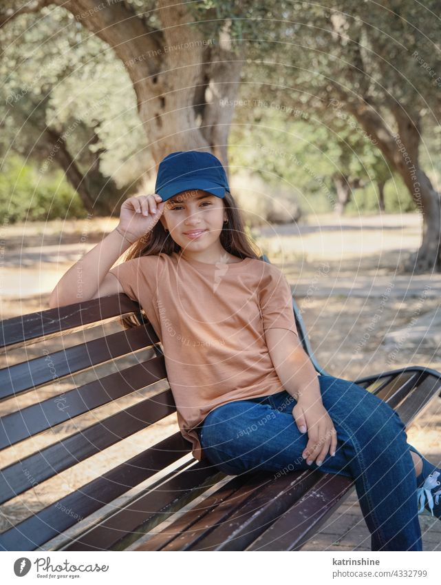 Smiling girl kid wearing t-shirt; jeans and baseball cap smile casual mock up bench park baseball hat child copy space Person Portrait preteen alone round neck