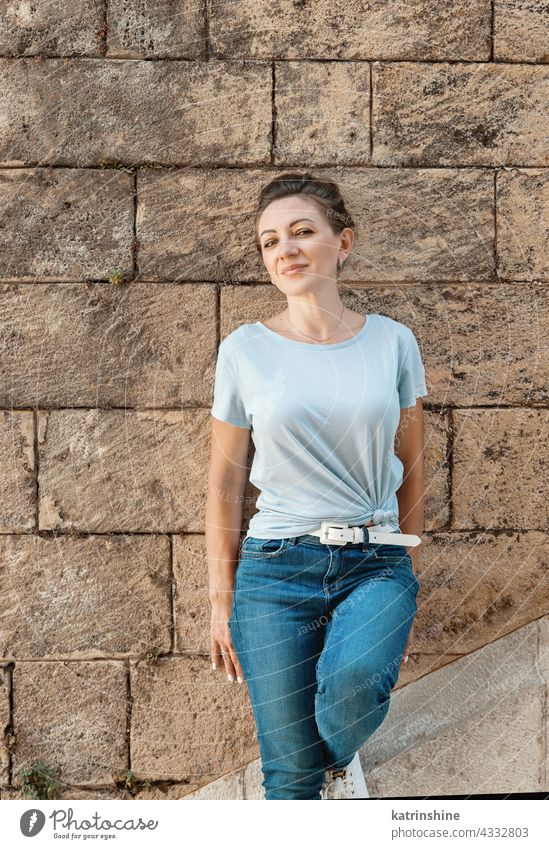 Women wearing t-shirt and jeans stays near a wall adult Middle aged women smile casual mock up Outdoor fair haired millennials copy space Person Portrait lady
