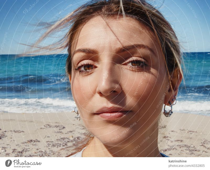 Young woman head close up Woman Close up Thoughtful Sea Beach Windy Alone Headshot face sky waves 20s 30s Lady young adult Portrait Blue Serious Lonely