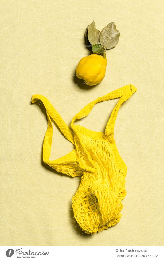 Quince apple and yellow mesh bag flat lay on linen natural quince shopping ripe leaf vitamin nature nutrition organic vegetarian quince fruit raw reusable