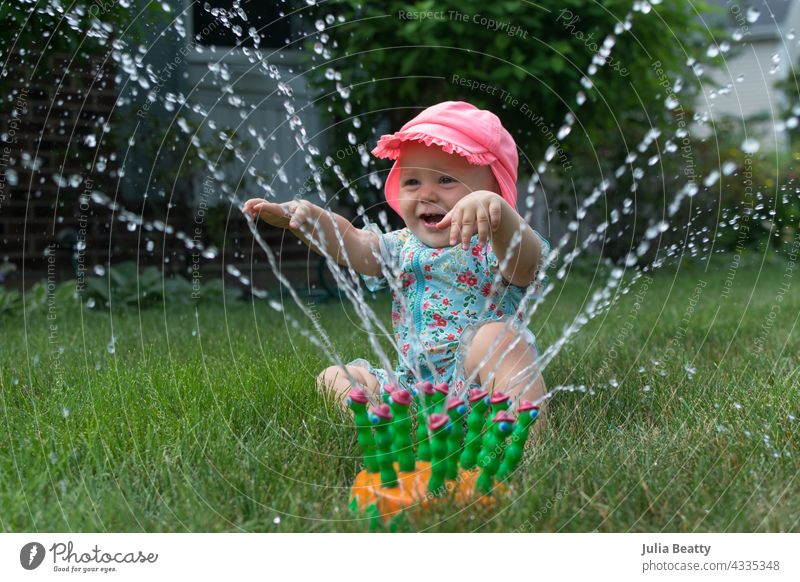One year old baby happily playing in sprinkler; simple water play entertainment for toddler sun safety yard home neighborhood midwest spf upf sun block clothing