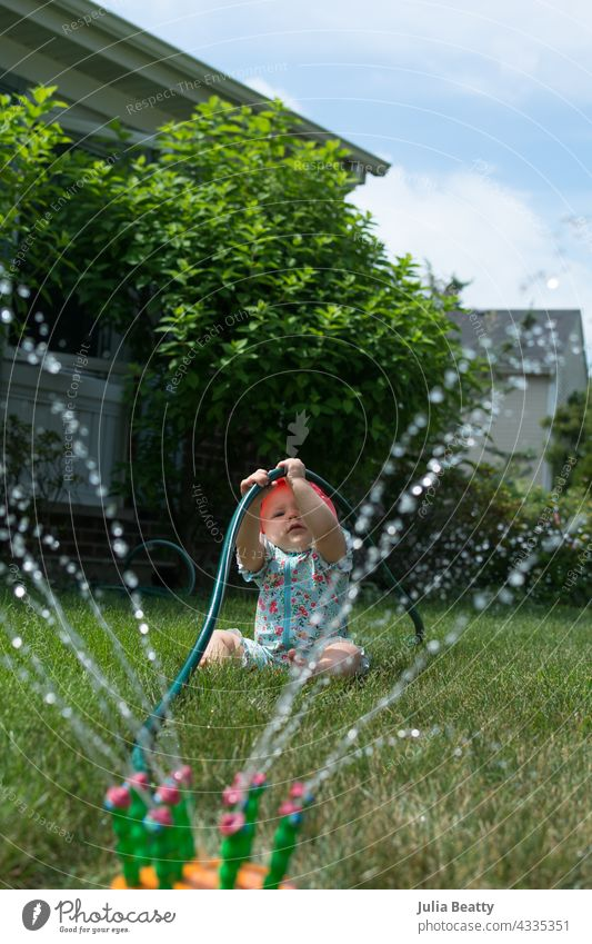 Young toddler hold onto garden hose while playing in sprinkler in front yard baby sun safety fine motor pull water water play home neighborhood midwest spf upf