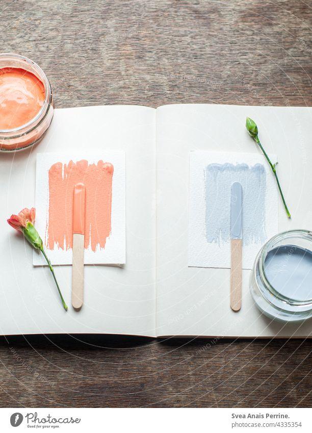 orange & light blue Colour wall paint Painting (action, artwork) Orange Light blue Blue Wood Wooden table flowers flatlay colour design Book Creativity