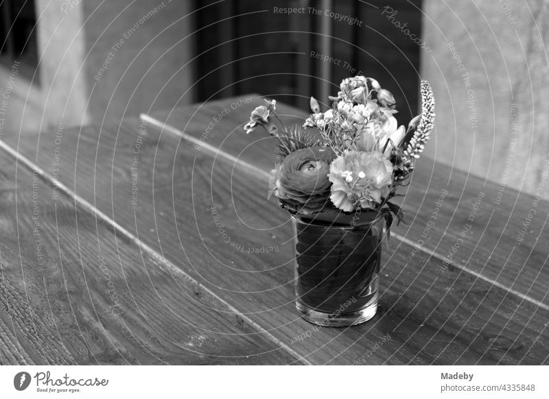 Simple drinking glass with flower decoration on a wooden table in front of a café in Braubachstraße in Frankfurt am Main in Hesse, photographed in neo-realistic black and white