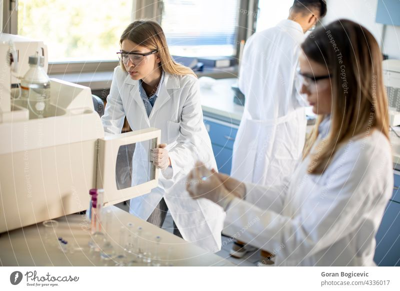 Female scientists in a white lab coat putting vial with a sample for an analysis on a ionchromatography system in biomedical lab automatic biochemistry