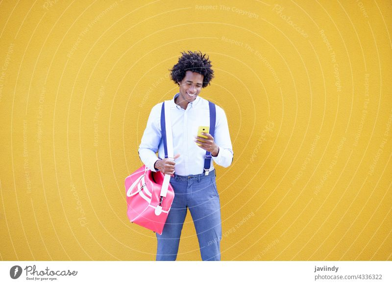 Black man with afro hairstyle carrying a sports bag and smartphone in yellow background. businessman black curly guy african portrait young smile commuter