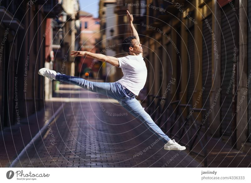 Black athletic man doing an acrobatic jump outdoors black street male cuban jumping young happiness person happy casual dancer lifestyle one adult acrobatics