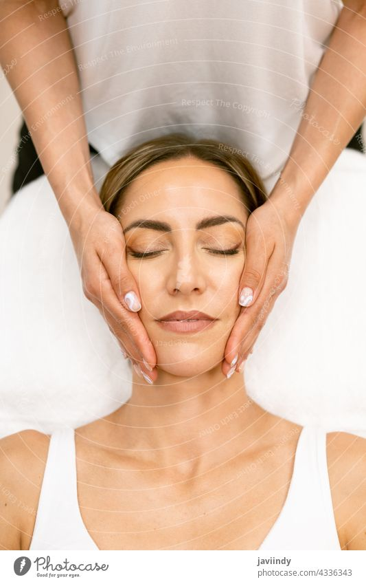 Middle-aged woman having a head massage in a beauty salon. female spa body relax massaging masseur wellbeing treatment care therapy wellness skin healthy
