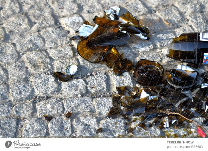 On beautifully set grey paving stones, the carelessly left shards of a brown bottle with a crown cap, shattered into a thousand pieces, form a picturesquely ugly contrast.