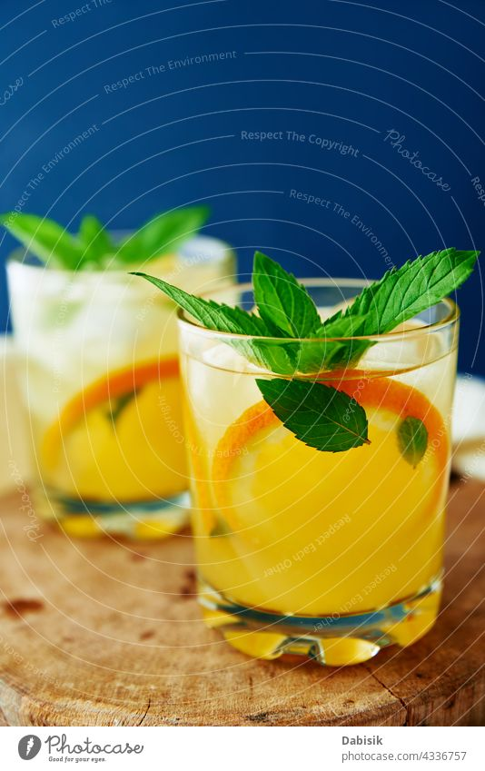 Orange fresh lemonade in glass on dark background drink orange summer cold citrus water fruit refreshing mint blue vitamin detox ice table beverage summer drink