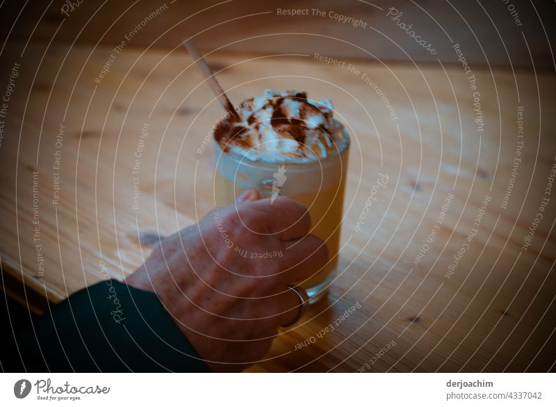 A refreshing drink is served, with cream and chocolate powder, over a wooden table. There is also a straw for the rest in the glass. Drinking Glass Beverage