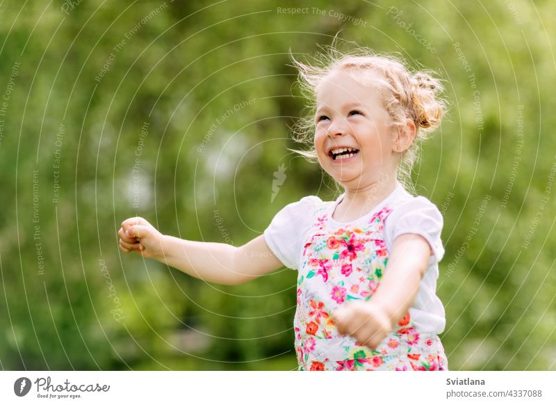 Happy laughing baby girl running in a clover fieldA happy laughing baby is running around the park or garden. Summer, summer time, happy days outdoor fun
