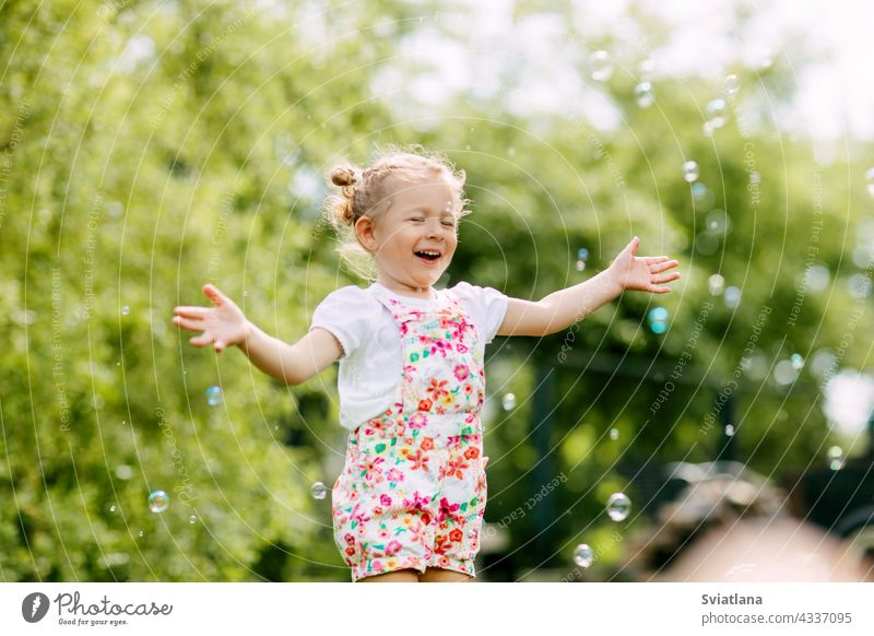A cheerful girl catches soap bubbles with her hands and laughs. Happy childhood, summer time little joy baby green fun portrait blow beautiful kid park play