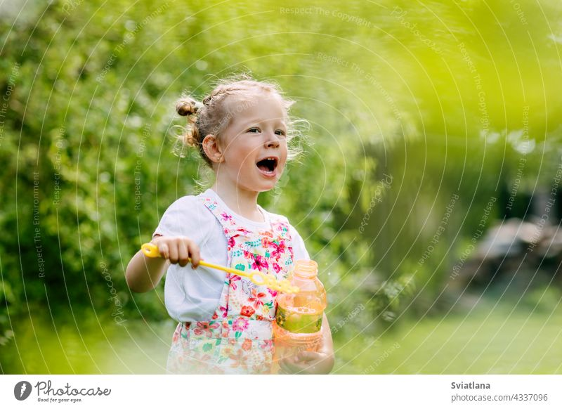 Charming baby girl with soap bubbles in the park or garden little joy childhood green fun portrait blow beautiful kid summer play cute nature funny blowing game