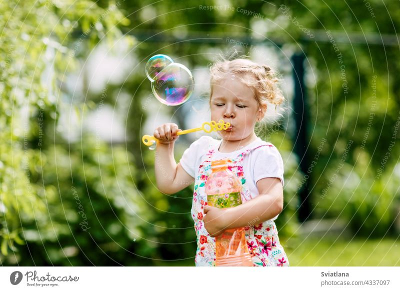 A little girl blows soap bubbles in the park. Happy childhood, summer time. Side view joy baby green fun portrait beautiful kid play cute nature funny blowing