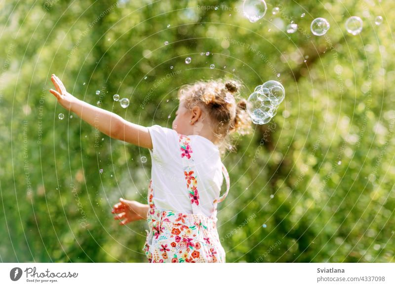 A cheerful girl catches soap bubbles with her hands. Happy childhood, summer time. Side view little joy baby green fun portrait blow beautiful kid park play